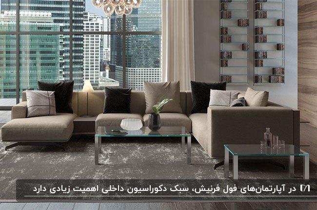 آپارتمانی فرنیش با مبل ال شکل کرم و کوسن های قهوه ای کنار پنجره های قدی
