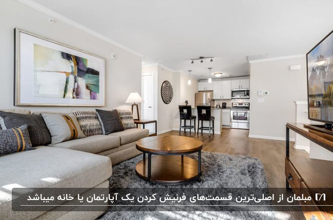 آپارتمان فرنیش با مبل ال شکل طوسی، میز گرد جلو مبلی و آشپزخانه کوچک سفید