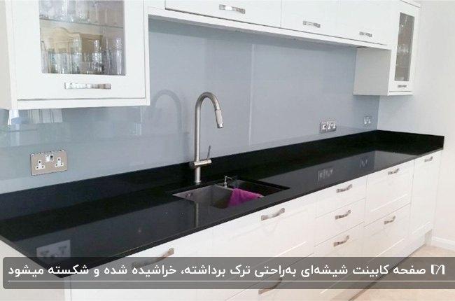 آشپزخانه ای با کابینت های سفید و صفحه کابینت شیشه ای مشکی