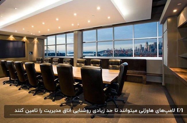 طراحی اتاق مدیریت بزرگی با میز جلسه مستطیلی و صندلی های چرخدار مشکی به همراه نورپردازی هالوژنی سقف