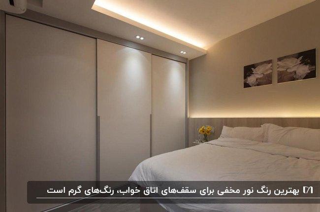اتاق خواب طوسی و سفیدی با تخت دو نفره ساده و نور مخفی ریسه ای و هالوژنی سقف