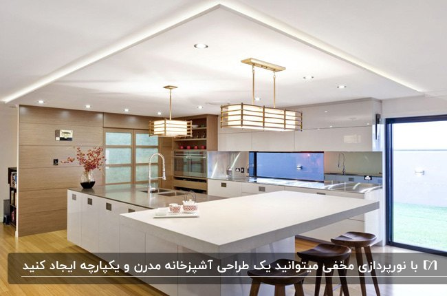 آشپزخانه ای با کابینت های سفید، چهارپایه های کانتر چوبی قهوه ای و نور مخفی سقف و دو لوستر آویز