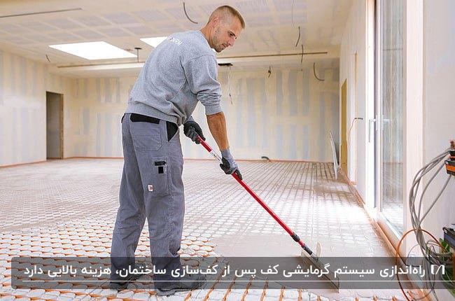 مردی در حال اجرای سیستم گرمایش از کف در خانه ای نیمه کاره
