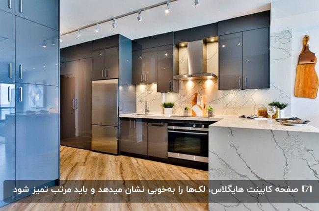 آشپزخانه ای با کابینت هایگلاس طوسی و آبی و صفحه کابینت هایگلاس سفید رگه دار