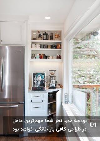 یک کافی بار خانگی در کنج بلااستفاده آشپزخانه کنار یخچال با کابینت و قفسه سه طبقه دیواری
