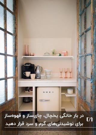 کافی بار خانگی با قفسه های سفید رنگ و یخچال کوچک برای نوشیدنی های سرد و قهوهساز برای نوشیدنی گرم