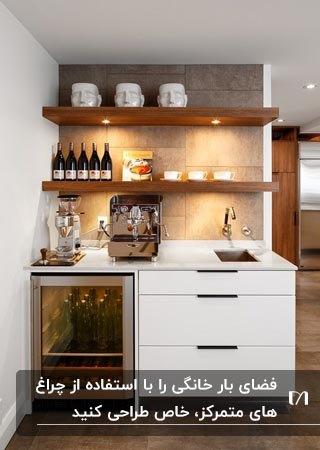 کافی بار خانگی با کابینت سفید و شلف های دیواری چوبی قهووه ای با نورپردازی هالوژنی