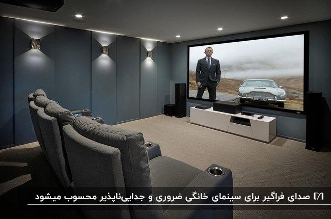 سینمای خصوصی خانه با دیوارها و مبلمان طوسی و سیستم صوتی باند