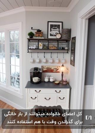 یک کافی بار خانگی با کابینت سفید و قفسه دیواری و یک چراغ رومیزی