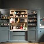 آشپزخانه ای مدرن با کابینت ها و دیوار خاکستری و سوپرمارکت داخل کابینت