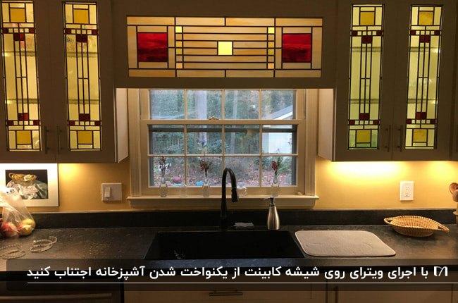 درب های شیشه ای با اجرای هنر ویترای برای کابینت های سفید یک آشپزخانه
