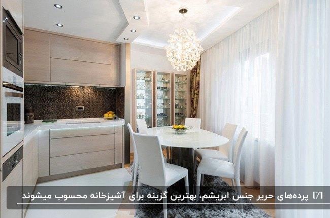 آشپزخانه بزرگی با کابینت های کرم رنگ، میز و صندلی های غذاخوری و پرده آشپزخانه حریر سفید