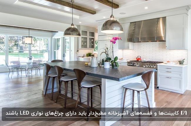 آشپزخانه مطبخ دار سفیدی با نورپردازی هالوژنی، نواری LED و لوسترهای آویز