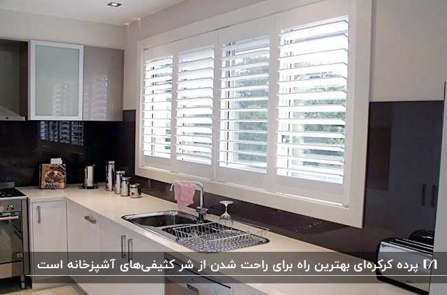آشپزخانه ای با کابینت های سفید، کاشی مشکی و پرده آشپزخانه کرکره ای سفید
