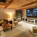 سینمای خصوصی خانه ای با سقف چوبی، کاغذدیواری طرحدار و مبل زیتونی رنگ