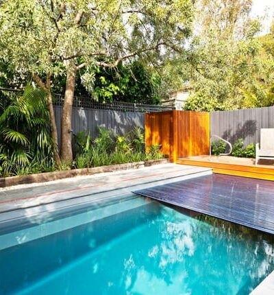 فضای سبز ویلایی با یک اتاقک چوبی، استخر مستطیلی و روکش استخر پنهان شونده
