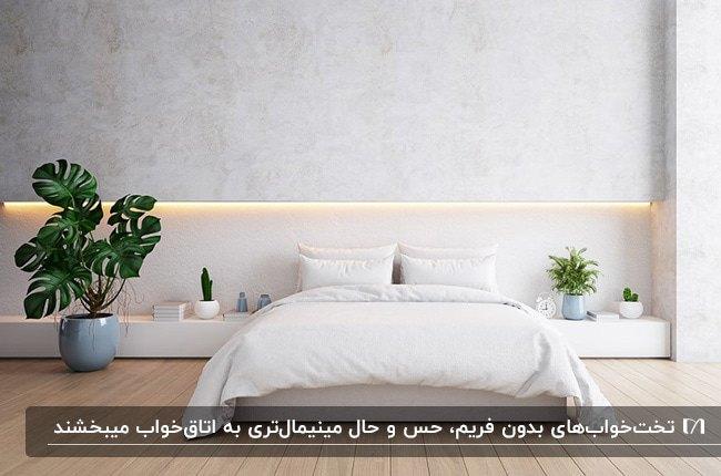 دکوراسیون مینیمال اتاق خوابی با تخت بدون فریم سفید و گلدان های گل اطراف تخت