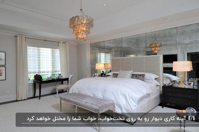 اتاق خوابی با تخت دو نفره طوسی، لوستر کریستال و آینه کاری دیوار پشت تخت