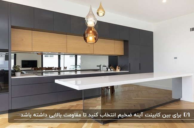آشپزخانه ای با کابینت های خاکستری و رنگ چوب و آینه کاری کانتر و بینت کابینت ها