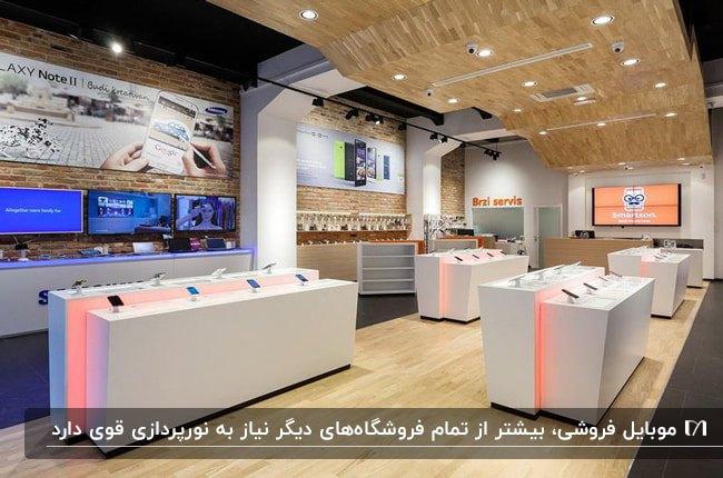 دکوراسیون مغازه موبایل فروشی با سقف کاذب چوبی، نورپردازی هالوژن و میزهای سفید