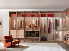 اتاق لباس مدرنی با قفسه های چوبی، باکس ها و صندلی راحتی قرمز رنگ