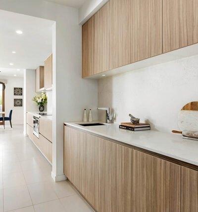 آشپزخانه مطبخ دار و مینیمالی با کابینت های رنگ چوب و رویه و بین کابینتی سفید