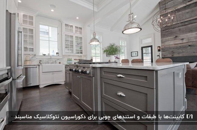 آشپزخانه ای به سبک نئوکلاسیک با کابینت های سفید و طوسی با درب شیشه ای