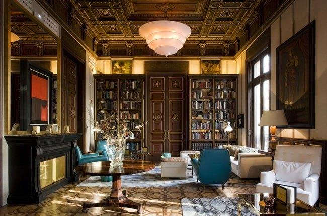 نشیمنی به سبک نئوکلاسیک با دیواری به عنوان کتابخانه و مبلمان شیری و آبی رنگ