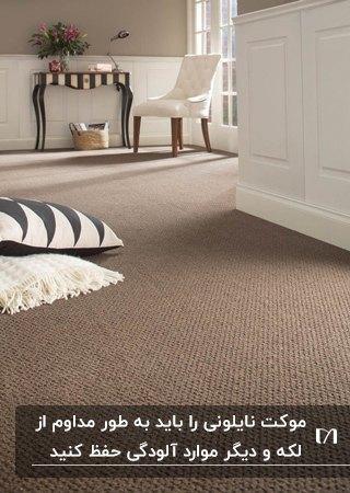 راهرویی با موکت نایلونی شکلاتی رنگ، دو کوسن و سفید و مشکی روی زمین و یک میز و صندلی انتهای راهرو