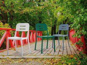 سه صندلی پلیمری با رنگ های سبز و آبی و سفید روی پل چوبی با نرده قرمز