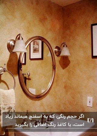 پتینه کاری با اسفنج برای دیوار نارنجی سرویس بهداشتی با آینه گرد و دو چراغ دیوارکوب