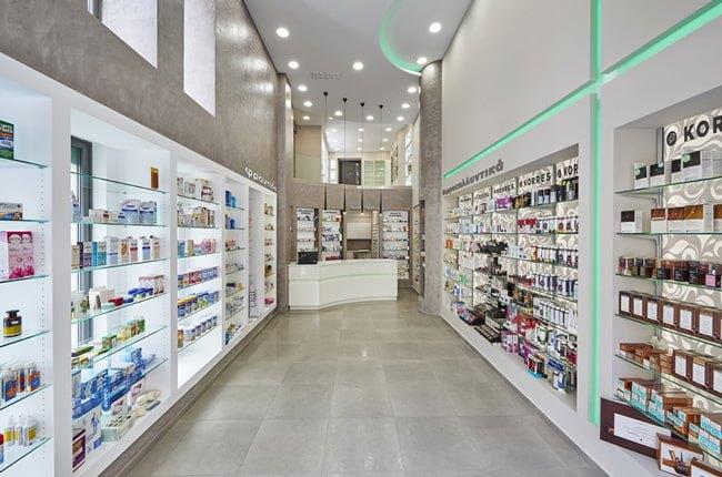 دکوراسیون داروخانهای با یک دیوار طوسی، کفپوش طوسی، قفسه های سفید و نورپردازی مخفی سبز رنگ