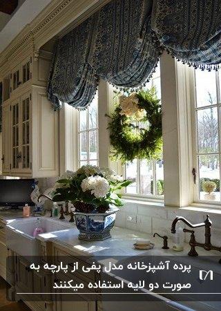آشپزخانه ای با کابینت های سفید و پرده آشپزخانه مدل پفی آبی رنگ