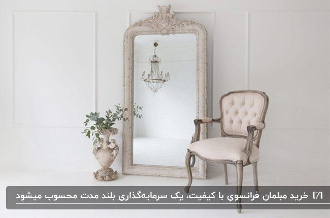 مبل فرانسوی و یک آینه قدی با فریم منبت کاری و یک گلدان طوسی
