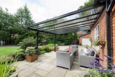 سقف شیشه ای با فریم فلزی مشکی حیاط خلوت و مبلمان حصیری طوسی و کوسن های سفید