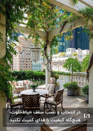 سقف شیشه ای حیاط خلوت آپارتمان با میز گرد و چهار صندلی چوبی