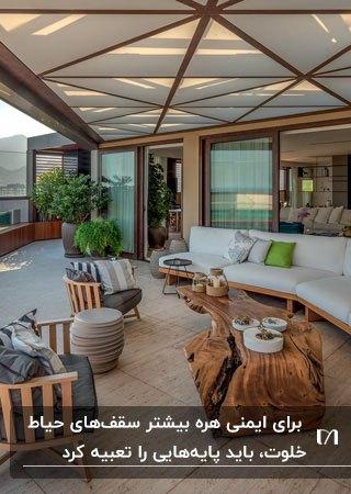 سقف حیاط خلوت با فریم چوبی، مبلمان، میز و صندلی های چوبی با پارچه سفید و خاکستری