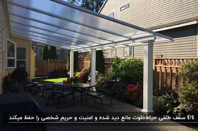 سقف طلقی مات برای حیاط خلوت با میز و صندلی های فلزی مشکی . گل های رنگی