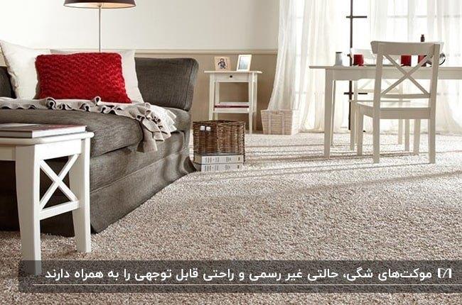 موکت شگی کرم رنگ در نشیمن با مبلمان خاکستری با کوسن قرمز و میز و صندلی های شیری