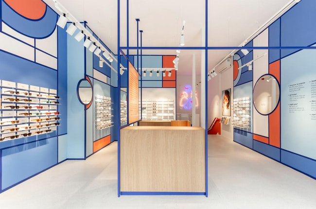 دکوراسیون مغازه عینک فروشی مدرن با ترکیب رنگ آبی و نارنجی با میز چوبی