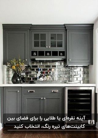 آشپزخانه ای با کابینت های خاکستری و آینه کاری نقره ای فضای بین کابینت