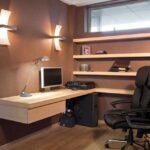 دفترکار کوچکی با دیوارهای قهوه ای، میز چوبی و دیواری ال شکل و قفسه های دیواری چوبی با صندلی مشکی