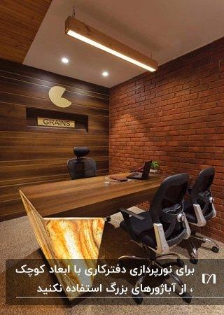 دفترکار کوچکی با دیوارپوش آجری و دیوارپوش چوبی، میز چوبی با نور مخفی . نورپردازی های سقف