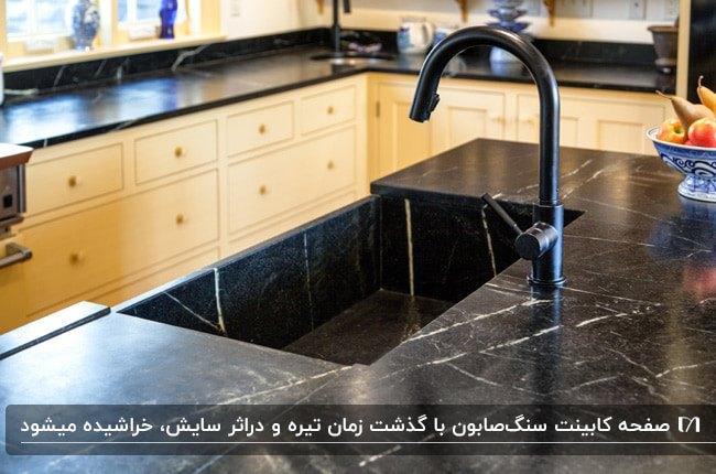 آشپزخانه ای با کابینت های کرم رنگ، شیرآلات مشکی و صفحه کابینت سنگ صابون مشکی با رگه های سفید