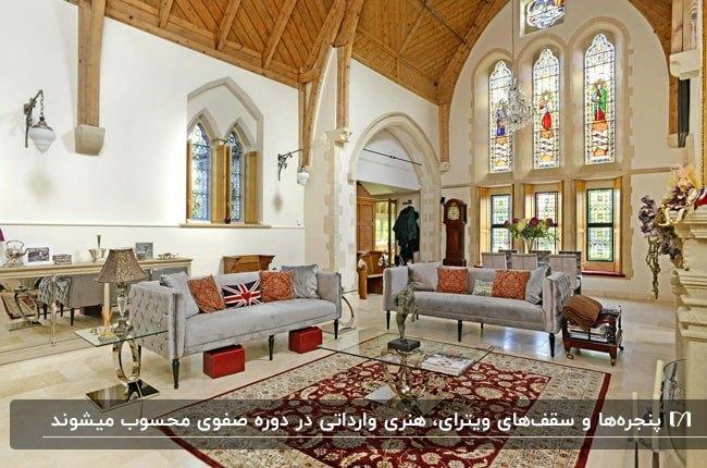 نشیمنی با سقف بلند منحنی، مبلمان طوسی و پنجره هایی که با ویترای طراحی شدند