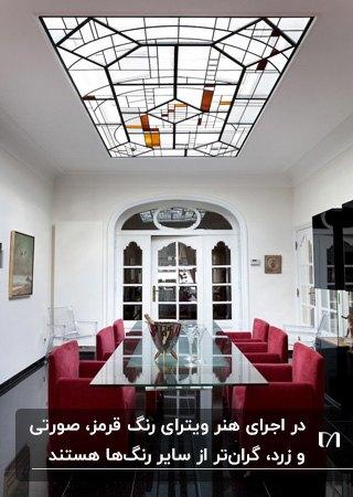 اتاق غذاخوری با میز شیشه ای و صندلی های قرمز به همراه سقف شیشه ای ویترای شده