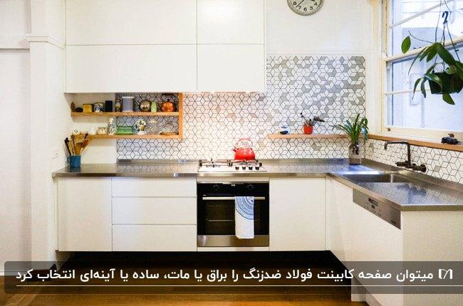 آشپزخانه ای با کاشی بین کابینتی طرحدار، کابینت سفید و صفحه کابینت فولاد ضد زنگ