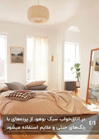 اتاق خوابی به سبک بوهو با تخت دو نفره، آینه قدی با فریم چوبی و پرده های حریر شیری رنگ