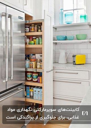 سوپرمارکت بلند کابینت با درب کشویی سفید رنگ برای نگهداری مواد غذایی کنار یخچال