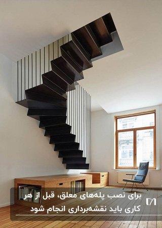 پله معلق فلزی مشکی رنگ با حفاظ مشکی و قفسه و کمد چوبی زیر راه پله